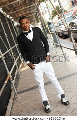 Young male model posing under scaffolding at Downtown Miami