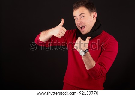Young male model wearing a red winter sweater and black scarf, showing thumbs up while smiling