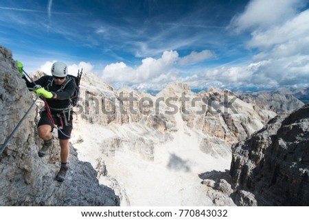 young male mountain climber dressed in black on a Via Ferrata in the Dolomites on a beautiful day in autumn