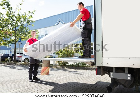 Young Male Movers Unloading The Wrapped Mattress From Moving Truck