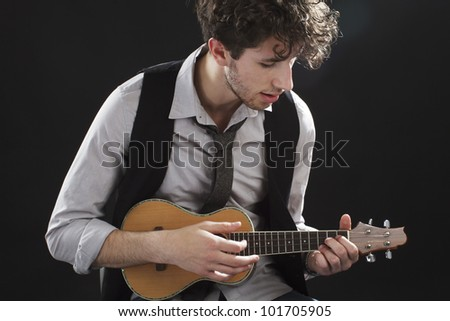 Young male musician sits and plays a ukulele. Backlighting, dark background, copy space, horizontal.