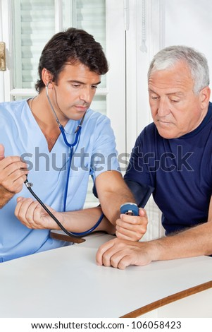 Young male nurse checking blood pressure of a senior man at hospital