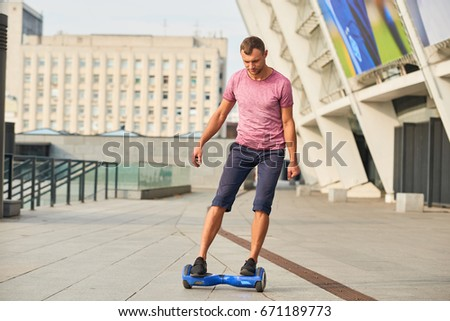 Young male on hoverboard outdoors. Man in the street. Best model of gyroscooter. #671189773