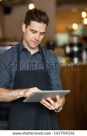 Young male owner using digital tablet while standing in shop