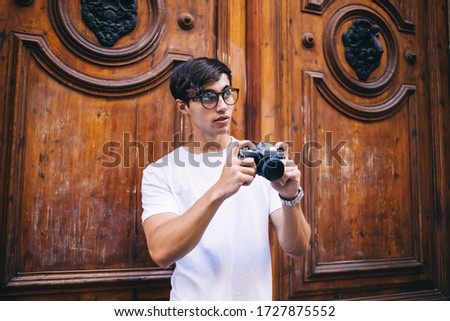 Photo of Young male photographer amateur in spectacles making pictures on town during free time, skilled hipster guy traveler in casual wear taking photos of historical places of city holding camera