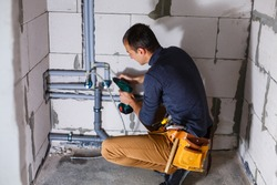 Young Male Plumber makes wiring of sewer pipes