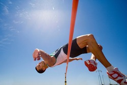 Young male pole vaulter jumping over a bar during a practice session at the track on a bright, sunny day with a clear blue sky in the background