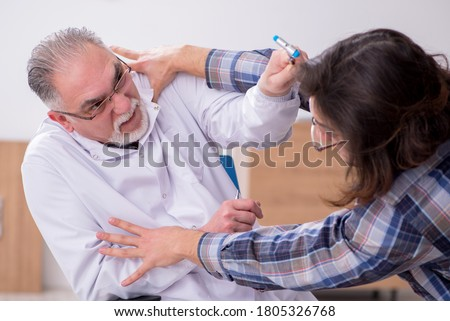 Young male psychopath and experienced doctor in madhouse Stock photo ©