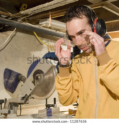 Young male putting on his safety goggles before using his power tools