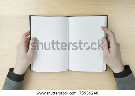 Young male reading an empty open book on a desk - insert your own message