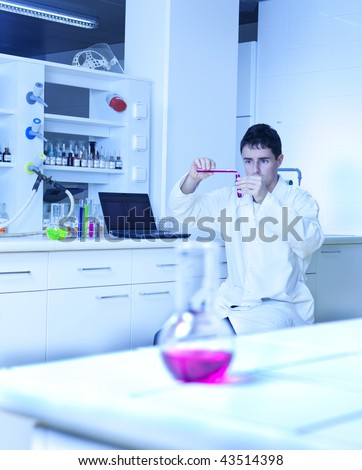 young male researcher carrying out experiments in a research lab (color toned image)
