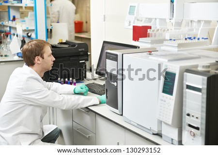 young male researcher works at computer scientific analysing data out scientific test in chemistry laboratory