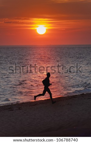 Young male runner running on a empty beach at sunset - stock photo