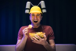 Young male sits on a sofa and eats snacks while watching a movie. Handsome man with beer helmet on the head watching TV and eating potato chips on the couch at home