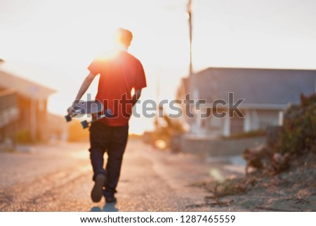 Young male skateboarder backlit by a sunset walks down a suburban street hill carrying a skateboard under his arm.