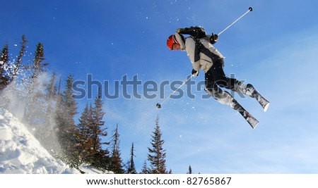 Young male skier jumping high and twisting on clear sky background - stock photo