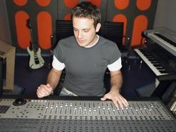 Young male sound technician in recording studio