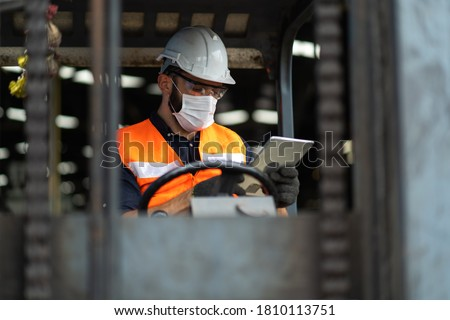 Young male staff driving forklift in warehouse. Worker man wearing face mask prevent covid-19 virus and protective hard hat. Industrial and industrial workers concept