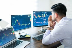 Young male stock broker praying for good fortune while trading online at desk from home