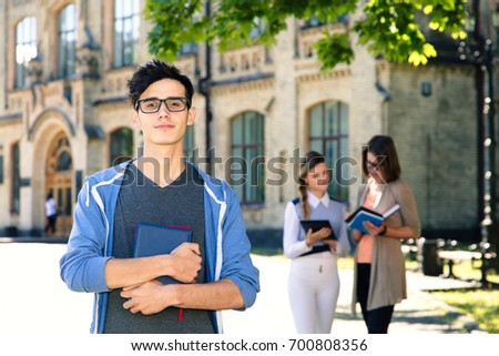 young male student holds...