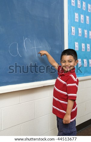 Young male student in front of blackboard with 'art' written on it. Vertically framed shot.