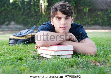 Young male student lying on grass with books