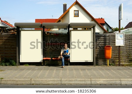 young male student sitting at bus stop with blank billboards