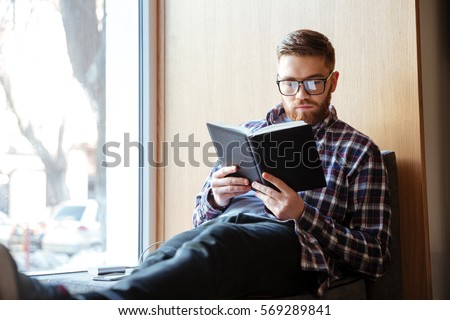 Young male student sitting on windowsill in library and reading book