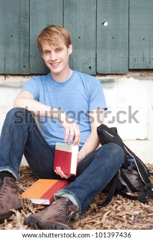 Young male student sitting with backpack and books