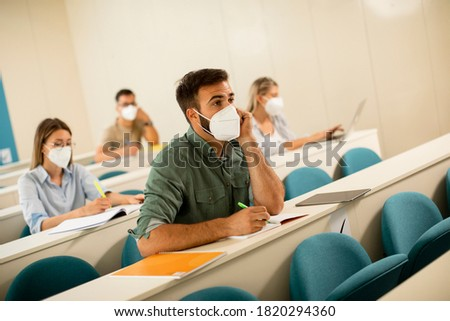 Young male student wearing face protective medical mask for virus protection at lecture hall Stock photo ©