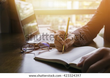 Young male student writes information from portable net-book while prepare for lectures in University campus,hipster man working on laptop computer while sitting in cafe,vintage color,selective focus