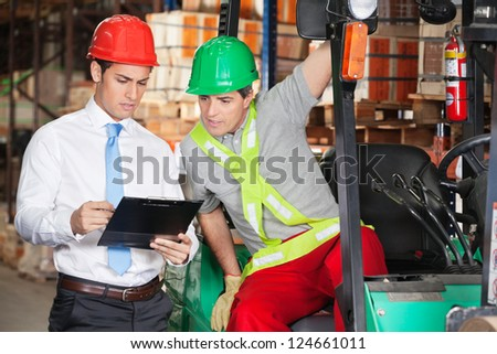 Young male supervisor showing clipboard to forklift driver at warehouse
