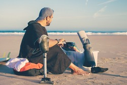 Young male surfer sitting near board on beach and changing artificial limbs. Side view. Artificial limb and outdoor activity concept