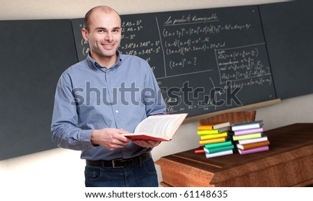 Young male teacher holding a book in a maths classroom
