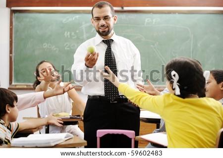Young male teacher with children in modern school, activities