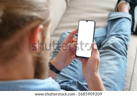 Young male tech user relaxing on sofa holding smartphone mock up blank white screen. Man customer using cell phone mobile social media or shopping app, reading news, sport betting. Over shoulder view
