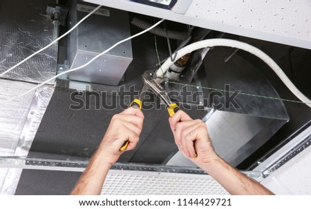 Young male technician repairing air conditioner indoors #1144429721
