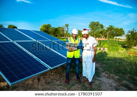 young male technician worker wearing green vests and helmet checks the maintenance of the solar panels and talking about installation of new solar panel with farmer at field, technology in agriculture