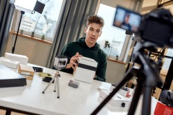 Young male technology blogger recording video blog or vlog about new camera lens and other gadgets at home studio. Blogging, Work from Home concept. Focus on person. Dutch angle. Horizontal shot