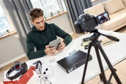 Young male technology blogger recording video blog or vlog about new tablet pc and other gadgets at home studio. Focus on a man. Blogging, Work from Home concept. Focus on person. Dutch angle