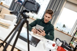 Young male technology blogger recording video blog or vlog about new tablet pc and other gadgets at home studio. Blogging, Work from Home concept. Focus on person. Dutch angle
