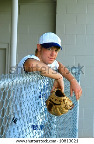 stock photo : Young male teen hangs over the dugout fence holding his ...