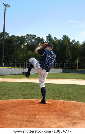 Young male teen winds up for the pitch.  Navy and white uniform.  Blue skies and baseball field.