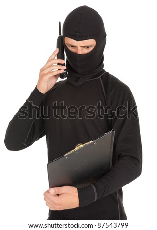 young male thief in balaclava with mobile phone and clipboard, white background