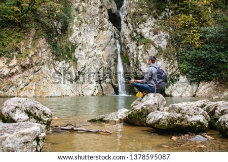 Young male tourist in casual clothes with backpack sits in picturesque place on stone overlooking waterfall and meditates alone. Concept of self-knowledge of self-improvement and self-identification