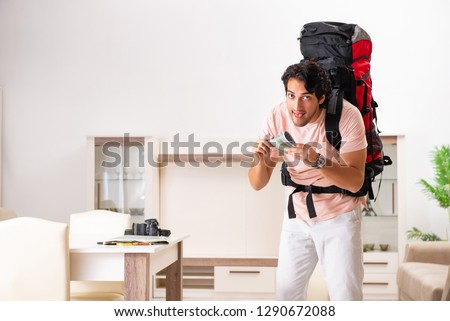 Young male tourist preparing for trip at home  #1290672088
