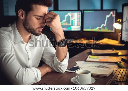 Young male trader at office work concept sitting closed eyes tired