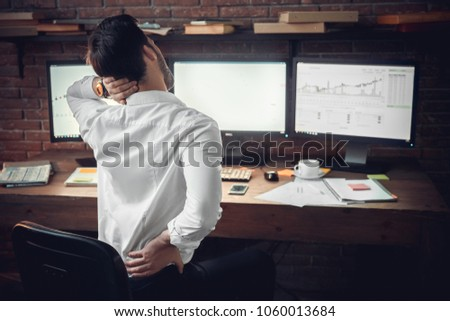 Young male trader at office work concept sitting muscle pain