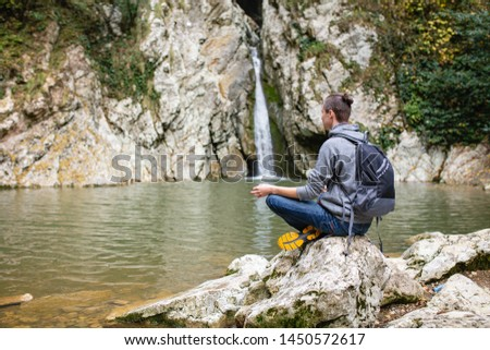 Young male travaler in casual clothes with backpack sits in picturesque place on stone overlooking waterfall and meditates alone. Concept of self-knowledge of self-improvement and self-identification