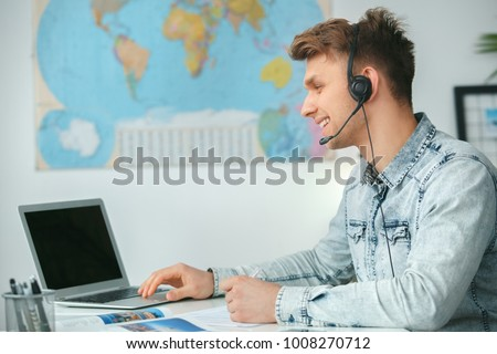 Young male travel agent consultant in tour agency using headset